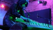 Michiyo Yagi is bent over a large koto stringed instrument in a pink light
