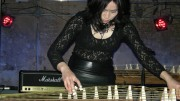Michiyo Yagi in a black lace top bends to pick the strings of the Koto