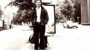 A black and white full portrait of Jack Halberstam, standing in a dusty street