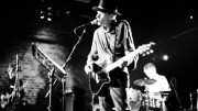 A B&W image of Jandek, in a hat, playing a guitar