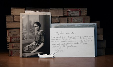 A vintage B&W photo of a woman next to a postcard that she has written