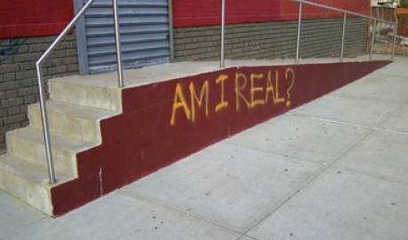 A read wall has the words AM I REAL spray painted in yellow paint