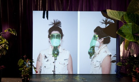 A white screen shows a double portrait of a woman wearing a gas mask