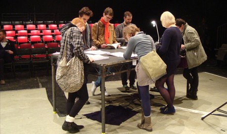 A group of people are standing gathered around a large black table reading