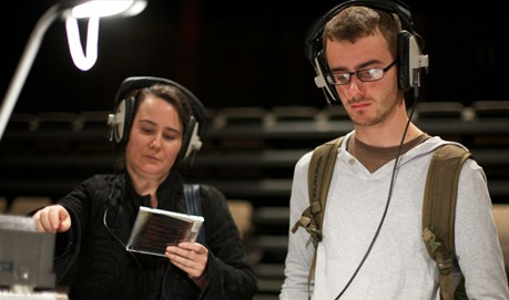 Two people stand at a table with headphones on listening. One holds a CD.