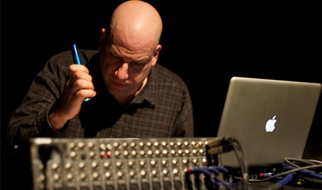 A man sits in front of a mixing desk and a compute with a torch