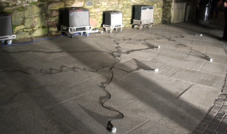 Several amps against a wall with microphones on long leads coming from each