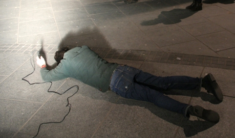 A man in a green jacket bangs a mic on the stone ground as he lies on the floor