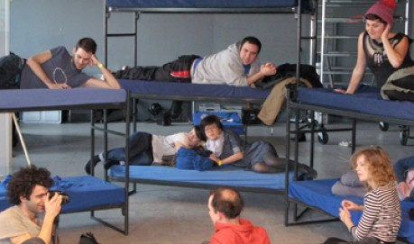 Several people lying on bunk beds, discussing