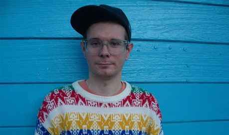 A person wearing a cap, glasses and colourful jumper