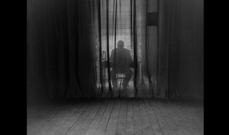 A film still. A silhouetted man sits behind a dimly lit curtain.