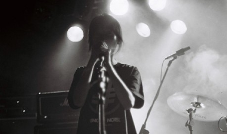 Junko sings into a microphone, lit from behind the image is in B&W