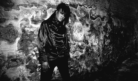 A B&W shot of M Lamar standing by a stone wall by flashlight