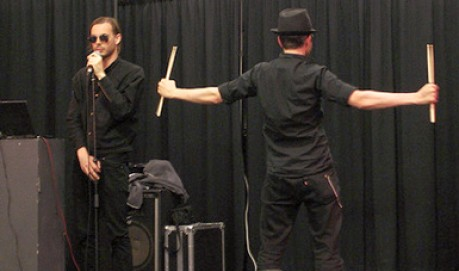In front of a black curtain, Mattin speaks into a mic, Tim holds aloft drumstick