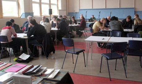 Several tables in a hall are surrounded be people taking part in a workshop.