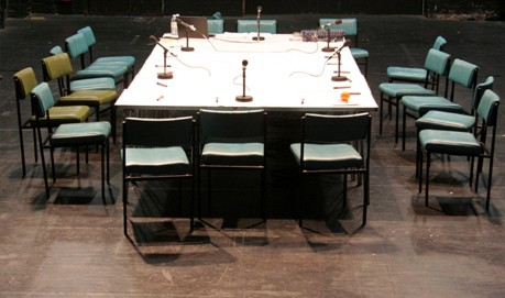 A rectangular white table in a black room in circled with green chairs
