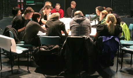 A large rectangular table is filled with people taking part in a workshop