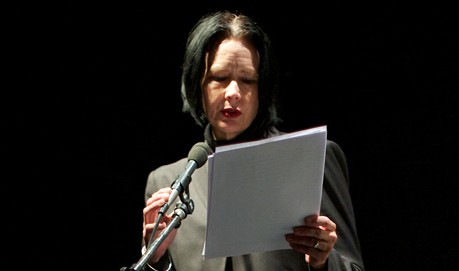 Against a dark background, Vanessa Place gives a reading