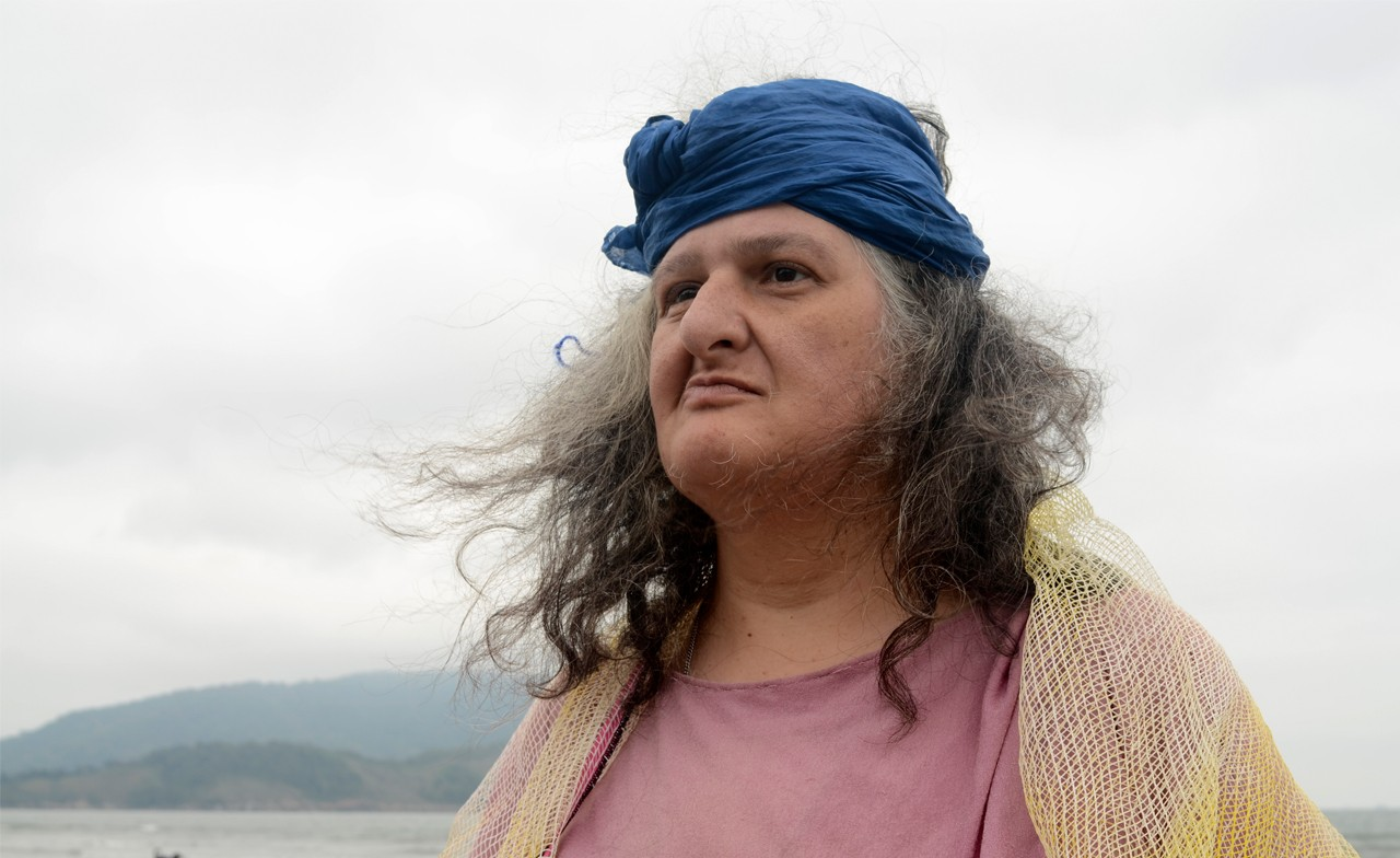 A member of Ueinzz wears a blue head wrap and looks out to sea