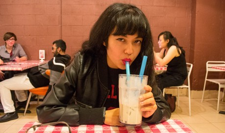Jackie Wang sits at a red and white checked table cloth sipping a milkshake