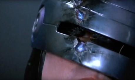 A Close up of a film still of RoboCops helmet and his eye beyond it
