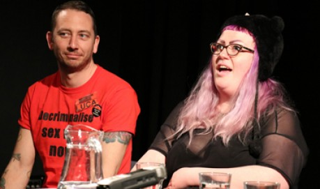 Two people sit on a panel one in a red t-shirt and another with pink hair