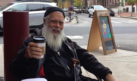 A bearded Samuel Delany raises a take away cup in a cheers as he smiles