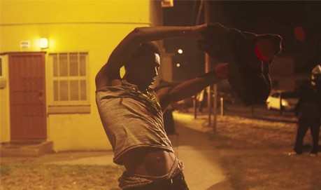 Storyboard P, lit by yellow street light by a street corner writhes his arms