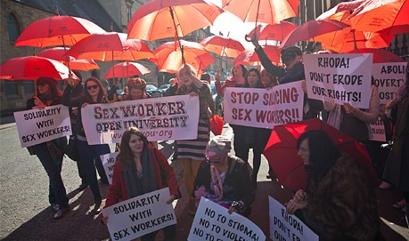 a group of people campaign for sex workers rights with banners and red umbrellas
