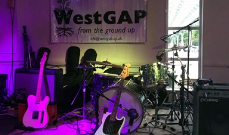 A shot of an purple lit stage with guitars set up and a WestGap banner