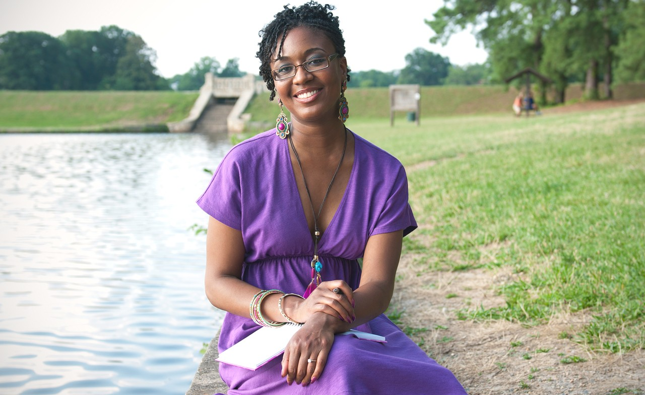 Camisha Jones smiles while sitting on a cement surface at the edge of a lake