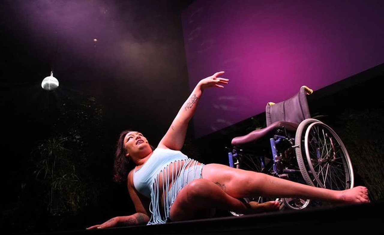 NEVE reclining dramatically on a pink lit stage infront of a manual wheelchair