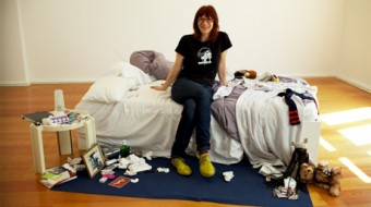 Ann Cvetkovich sits on an unmade bed, in an otherwise empty room