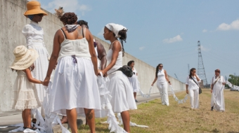 people dressed in white dresses & summer hats standing in a circle