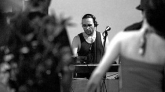 A black and white action shot of DJ Sprinkles djing for dancers