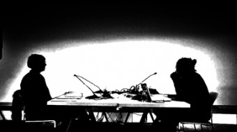 B&W image from the side of two people silhouetted as they sit at a table