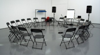 A white room with a circle of black chairs, a flip chart easel and two speakers