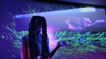 A person DJ with purple and green images projected behind them