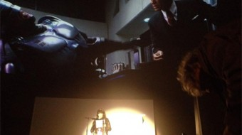 A reader in a spotlight is dwarfed by a screen with scenes from RoboCop