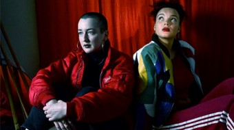 Two people in natty jackets sit in front of a red curtain