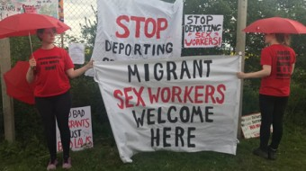 Two people holding red umbrellas and banners: Stop deporting Migrant Sex Workers