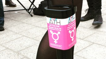 A shot of a collecting tin with a Pink sticker that says Action for Trans Health