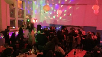A large group of people at table mill and dance in a room lit with party lights