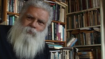 A beard Samuel Delany sits in front of a wall of shelves full of books
