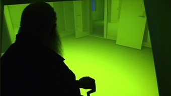 A silhouette of Delany in front of screen where a room is lit with green light