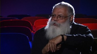 A bearded Delany leans on a seat back as he talks in a cinema space