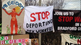 "handmade banners on a fence, one reads ""Stop Deporting Sex Workers"""