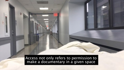 A film still shows an interior view along a hospital corridor: