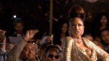 A woman performs in a gold dress, a mid shot, walking down a ballroom runway