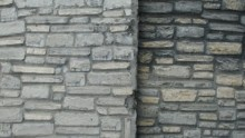 A wall made of grey, uneven bricks of natural stone